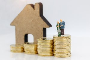 Miniature elderly couple figurines standing on coin piles in front of a small house cut out