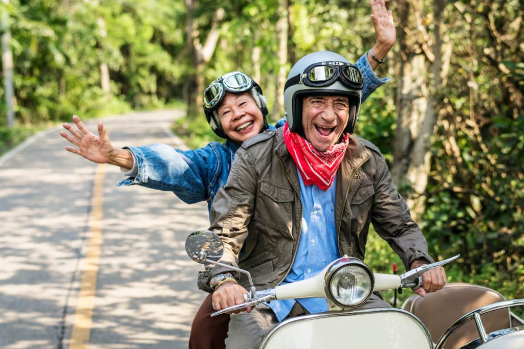 Retired couple driving a scooter together