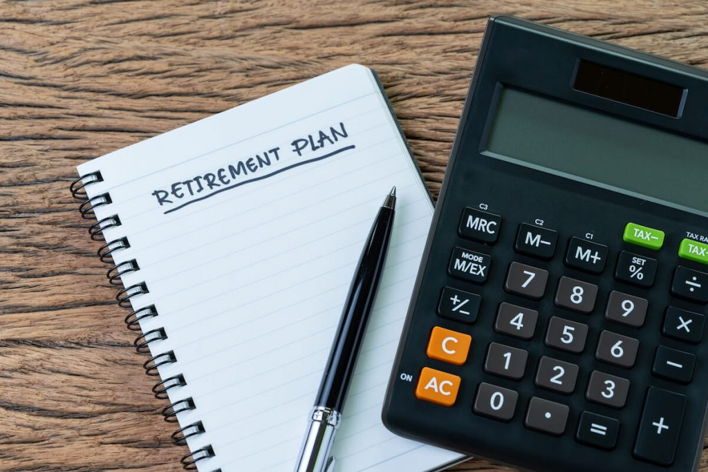 Retirement plan brainstorm on notebook and calculator