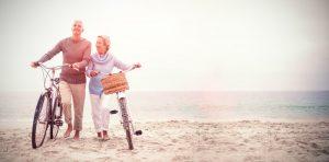 retiree couple enjoying bike ride on the beach
