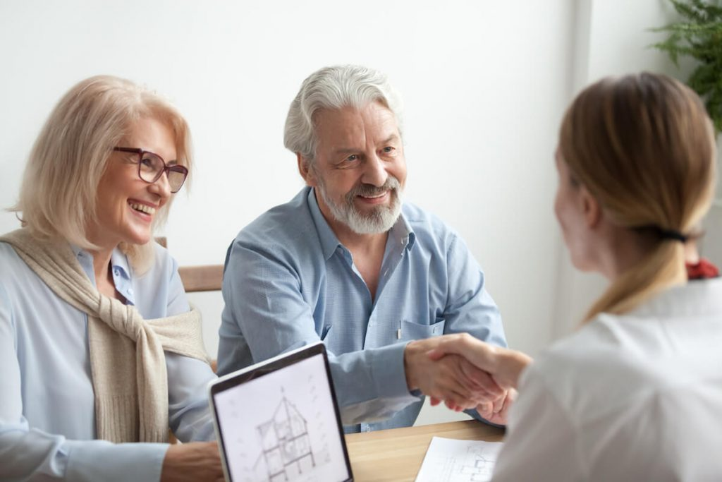 Retired couple shaking hands after purchasing property
