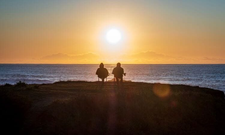 old couple watching sunset by the sea